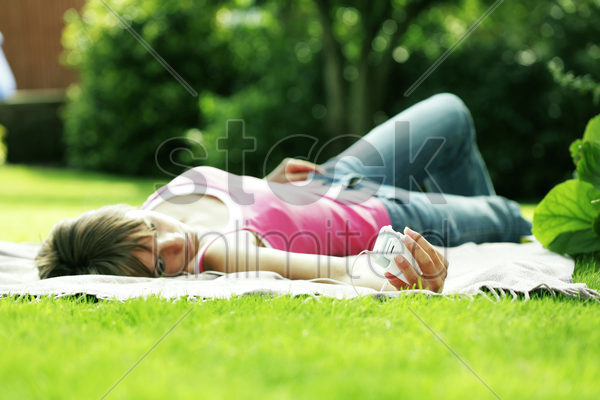 teenage girl lying on the field listening to music on a portable mp3 player stock photo