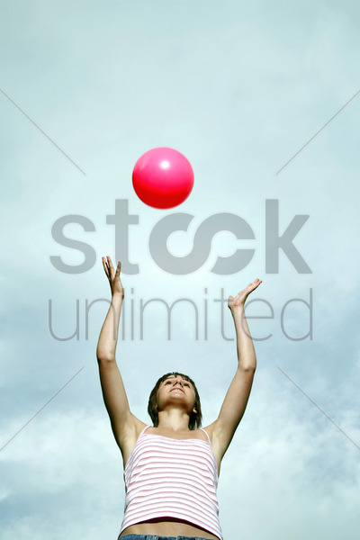 teenage girl playing with a ball stock photo