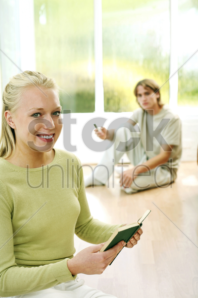 teenage girl reading book with her boyfriend holding mobile phone in the background stock photo