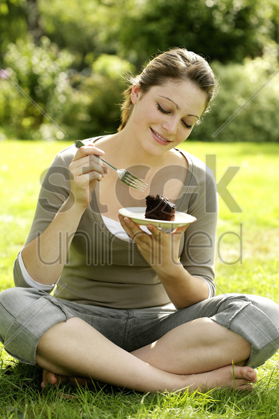 teenage girl sitting on the field enjoying a piece of cake stock photo