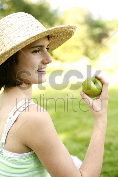 teenage girl sitting on the field holding a green apple stock photo