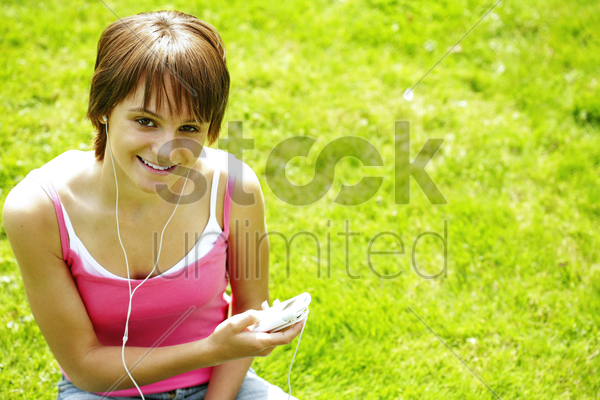 teenage girl sitting on the field listening to music on a portable mp3 player stock photo