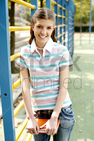 teenage girl smiling while holding a book stock photo