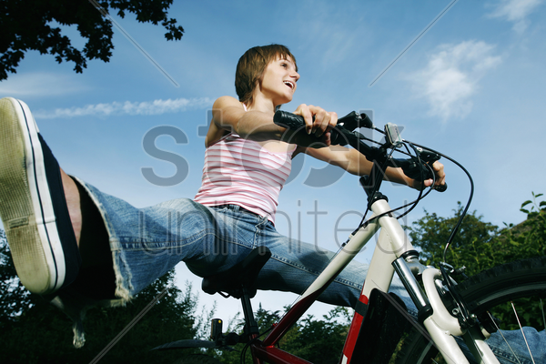 teenage girl spreading her legs while sitting on bicycle stock photo