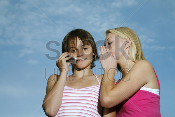 teenage girl talking on the phone with her friend whispering into her ear stock photo