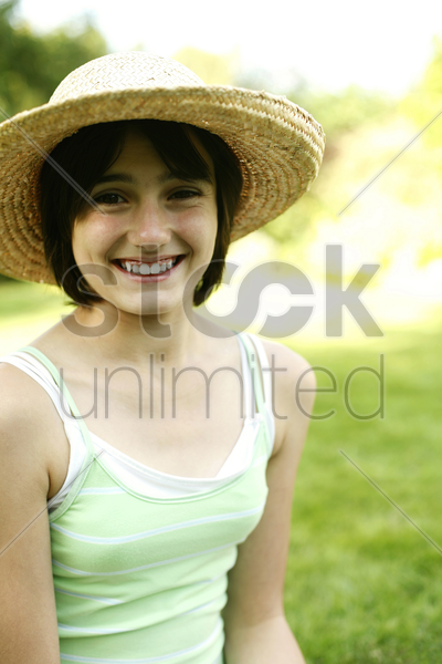 teenage girl with hat sitting on the field stock photo