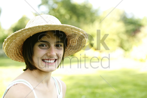 teenage girl with hat smiling at the camera stock photo
