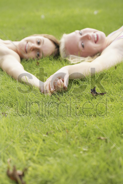 teenage girls holding hands while lying on the field stock photo