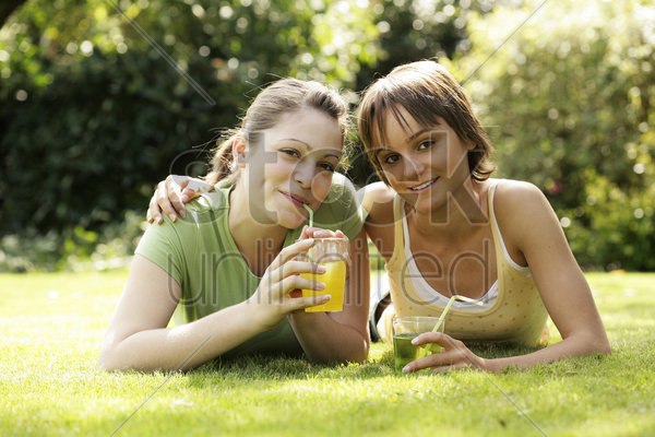 teenage girls lying forward on the field enjoying their drinks stock photo