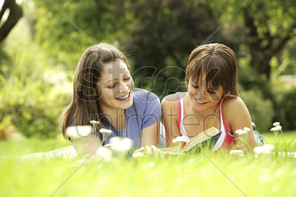 teenage girls lying forward on the field reading book stock photo