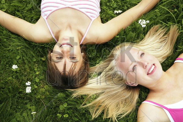 teenage girls lying on the field stock photo