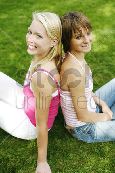 teenage girls sitting on the field smiling stock photo
