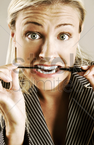 tensed up woman biting a pen stock photo