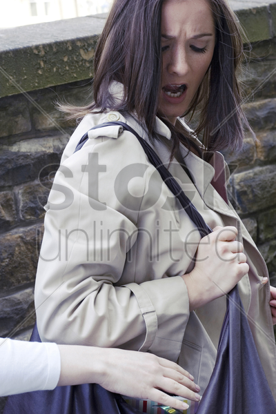 thief stealing from a woman's handbag stock photo
