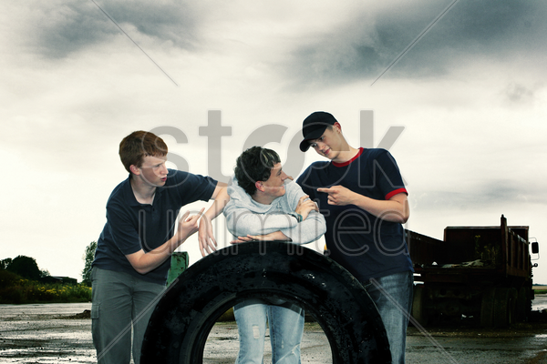 three boys posing with a big tyre stock photo