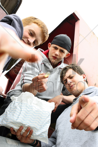 three boys sharing a packet of french fries stock photo