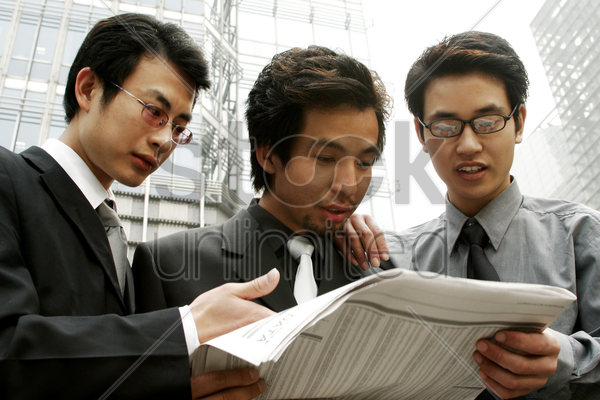 three businessmen sharing a newspaper stock photo