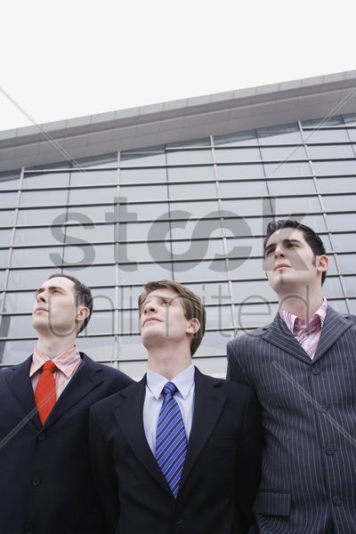 three businessmen standing in a row stock photo