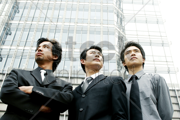three businessmen standing in front of the building stock photo