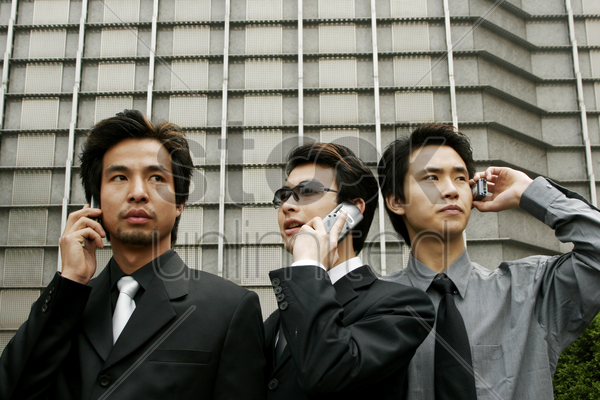 three businessmen talking on the hand phones stock photo