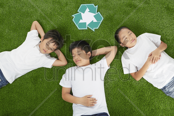 three children lying on the grass with eyes closed stock photo