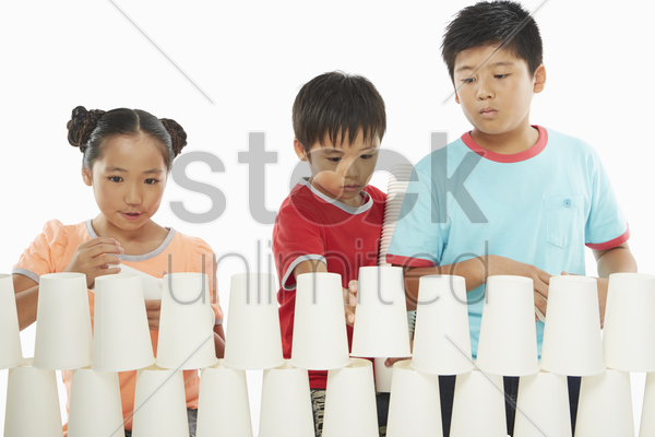 three children stacking up disposable cups together stock photo