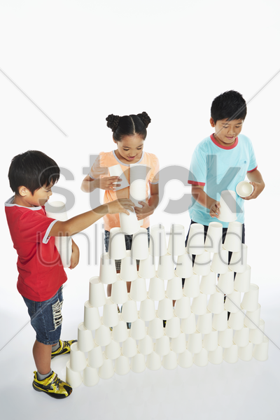 three children stacking up disposable cups stock photo
