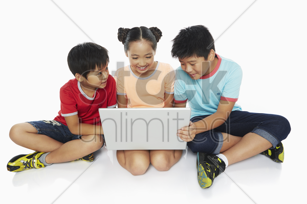 three children using a laptop together stock photo