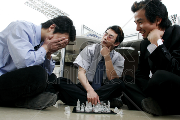 three men playing chess in the office stock photo