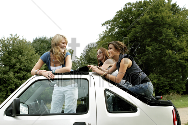 three women posing on a car stock photo