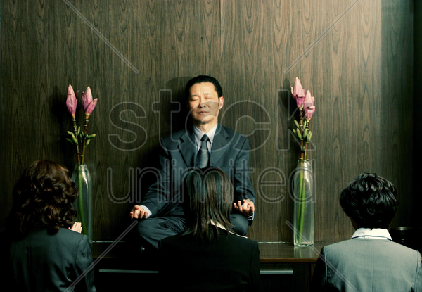 three women praying in front of a meditating man stock photo