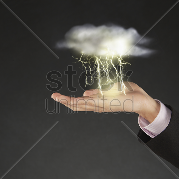 thunder and lightning striking above human hand stock photo