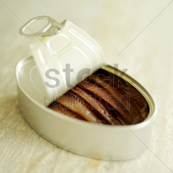 tin of anchovies on rough marble with lid peeled back stock photo