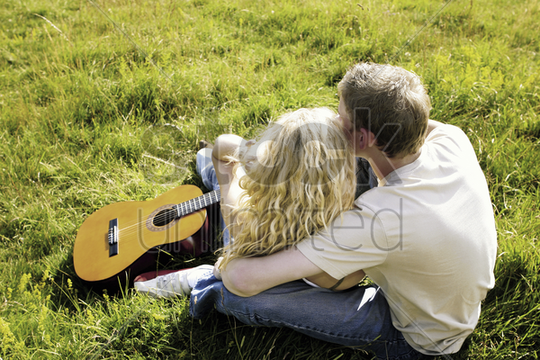 top angle view of a couple sitting on the grass hugging stock photo