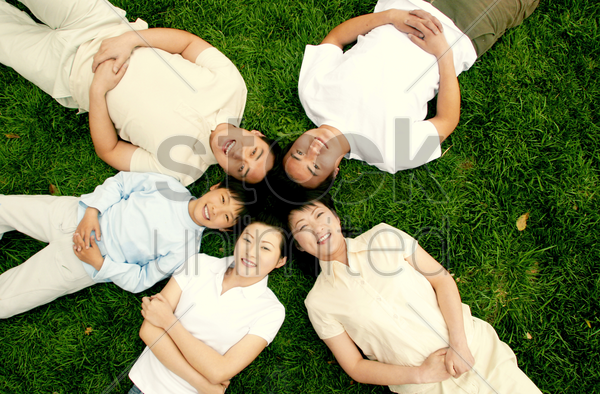top angle view of a family lying on the grass in circle stock photo