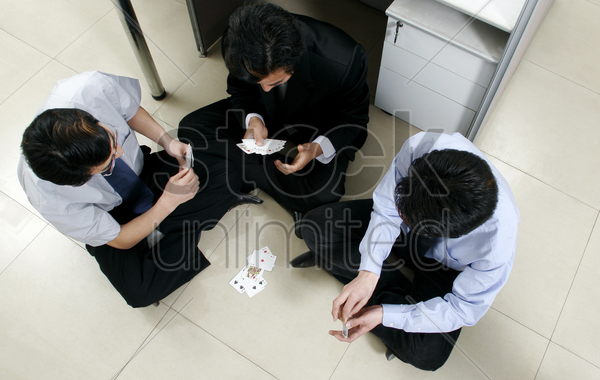 top view of three men playing cards in the office stock photo