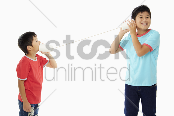 two boys playing with a paper cup phone stock photo