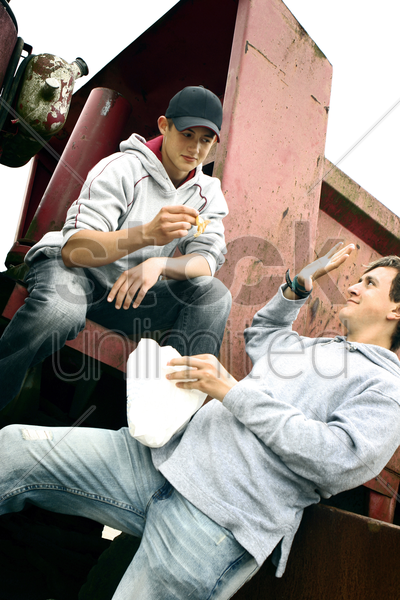 two boys sharing a packet of french fries stock photo