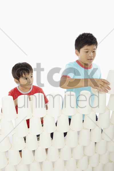 two boys stacking up disposable cups together stock photo