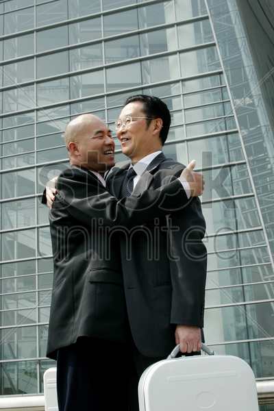 two businessmen hugging each other stock photo