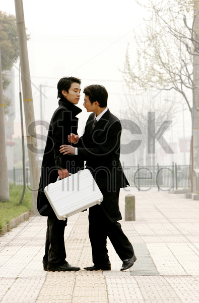 two businessmen pushing each other stock photo