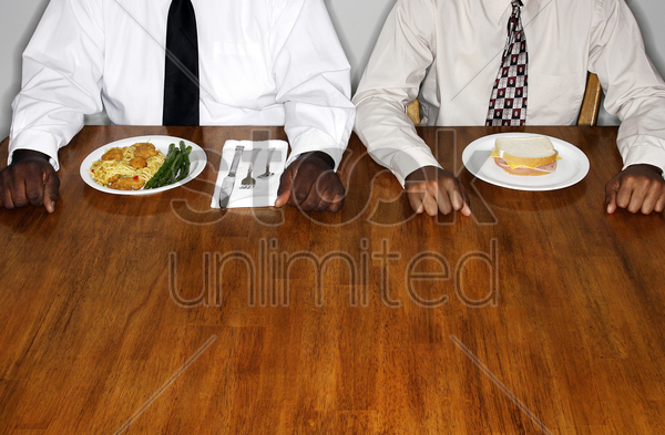 two businessmen with two different meals stock photo