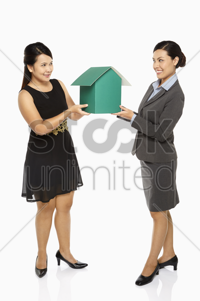 two businesswoman holding up a cardboard house stock photo