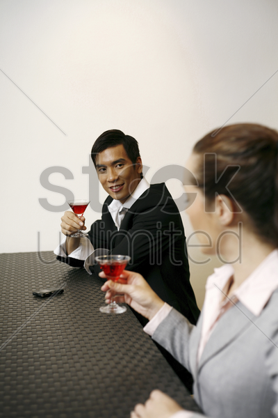 two colleagues enjoying cocktails stock photo