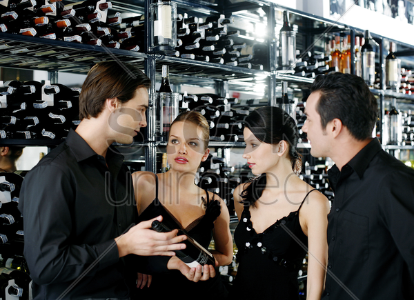 two couples choosing wine in the wine cellar stock photo