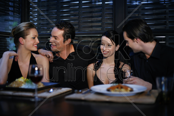 two couples having dinner together stock photo