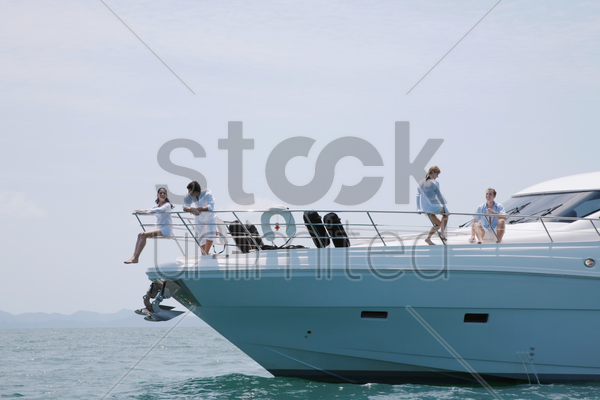 two couples relaxing on yacht stock photo