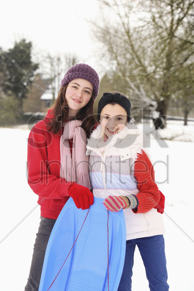two girls getting ready to go sled riding stock photo