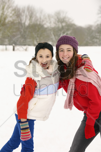 two girls having fun in the snow stock photo