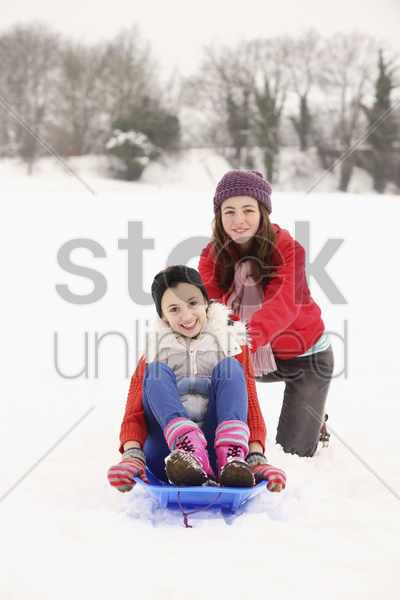 two girls playing in the snow, riding sled stock photo